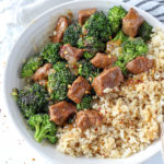 instant pot beef and broccoli in a white bowl with a white and black striped towel