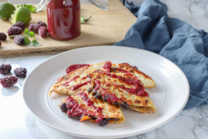 black bean quesadillas with blackberry enchilada sauce on a stone plate on a blue napkin