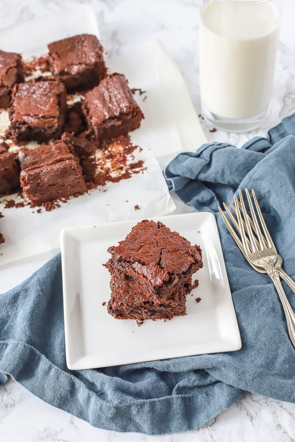 two healthy brownies stacked on a white plate on a blue napkin with two vintage forks to the right