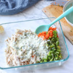 chicken, carrots, and peppers in a glass dish with mayo mixture or it to make chicken salad