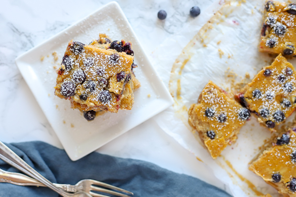 blueberry lemon bars on a white plate and dusted with powder sugar. More sliced bars on the right on top of parchment paper
