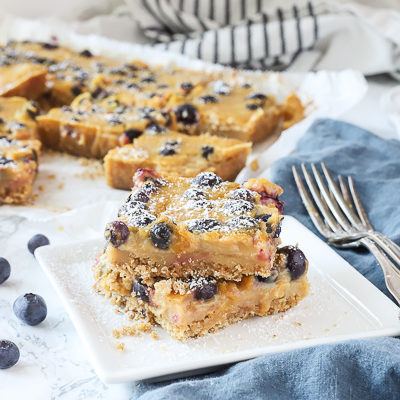 blueberry lemon bars stacked on a white plate with more dessert bars behind them