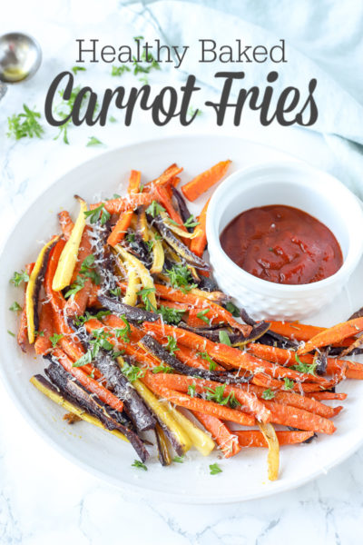 colorful baked carrot fries sprinkled with parsley and cheese on a white plate with ketchup