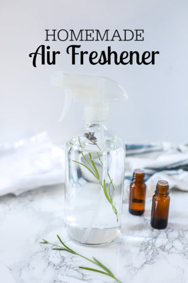 homemade air freshener in a glass spray bottle with lavender inside. Essential oils and a white and blue napkin are behind it