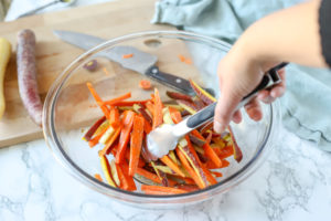 tossing oil into sliced carrots in a glass bowl
