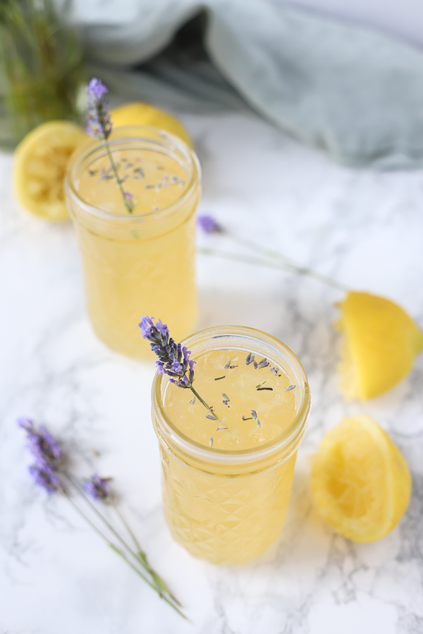 2 glasses of lavender lemonade with lemons ad fresh lavender around it