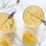 overhead shot of two glasses of lavender lemonade with dried lavender sprinkled in and a sprig of fresh lavender