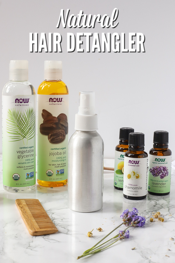 Natural hair detangler in spray bottle with essential oils and other ingredients around