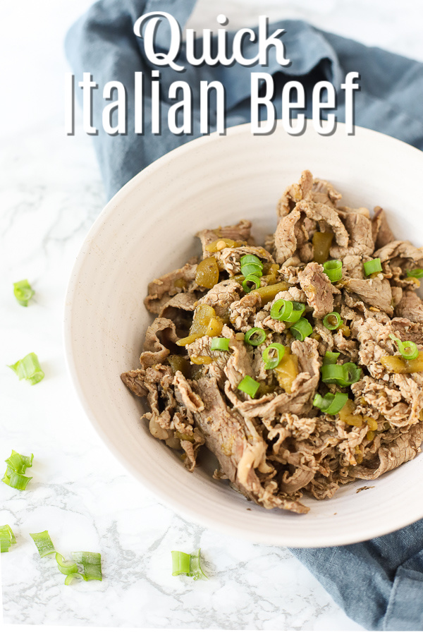 Chicago style Italian Beef in a white bowl and topped with green onions