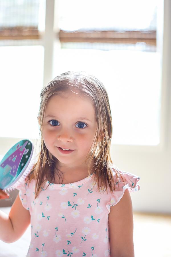girl brushing wet hair wearing pink dress