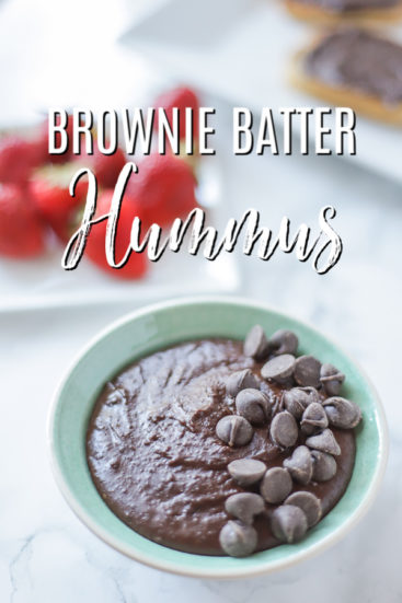 bowl of brownie batter hummus topped with chocolate chips with strawberries behind it