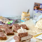 homemade double chocolate energy bars stacked up with more bars and ingredients behind it