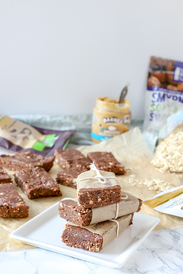 homemade double chocolate energy bars stacked up with more bars and ingredients behind it - healthy snack ideas for kids