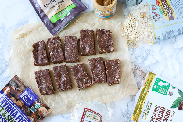 homemade energy bars sliced on parchment paper with ingredients arount it