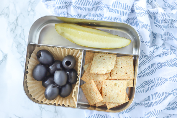 bento box with crackers, olives, and a pickle