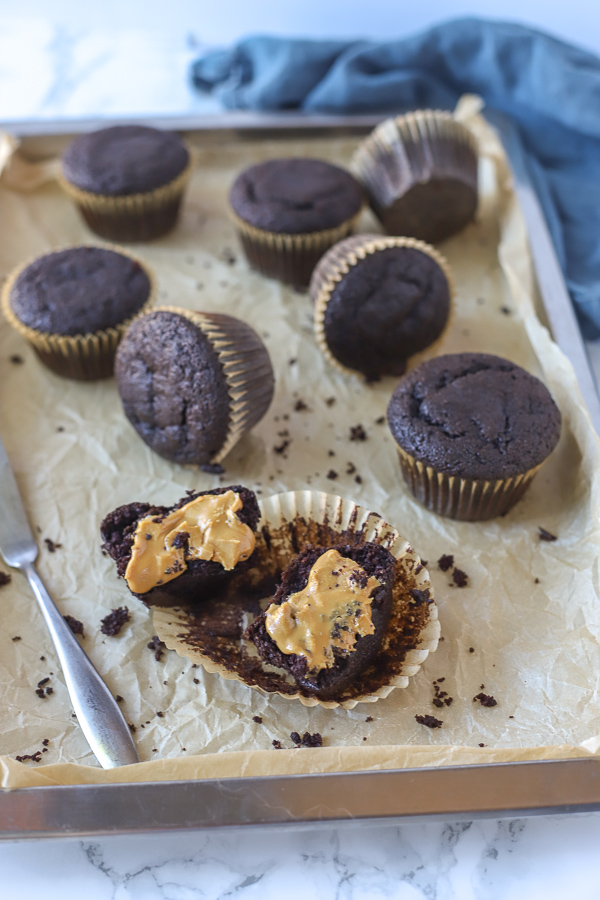muffins on a baking sheet with one muffin sliced and spread with almond butter