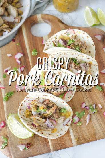 four pork carnita tacos stacked together on a wood cutting board