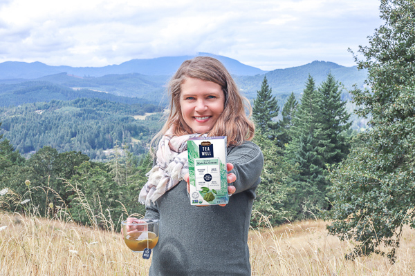 women in green sweater with the mountain in the background holding a box of teawell tea in one hand and a mug in tea in the other