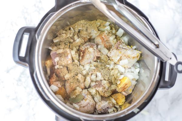 adding seasoning to pork tenderloin in the pressure cooker for pork carnitas