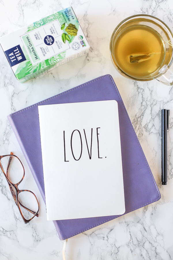 two journals stacked up with glasses to the left and a mug of TeaWell tea behind. Self-Care Tips