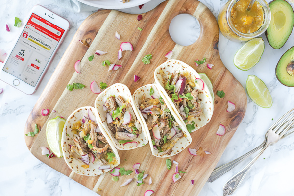 four pork carnitas on a wood cutting board with a phone to the left with the Safeway App
