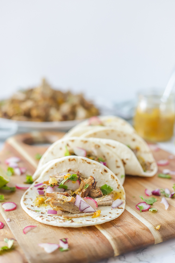 four pork carnita tacos stacked side by side on a wood cutting board with ingredients scattered around