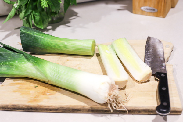 prepping leeks for potato leek soup on a cutting board with a knife