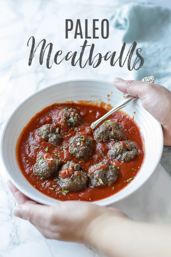 hands holding a cream bowl full of meatballs and marinara sauce