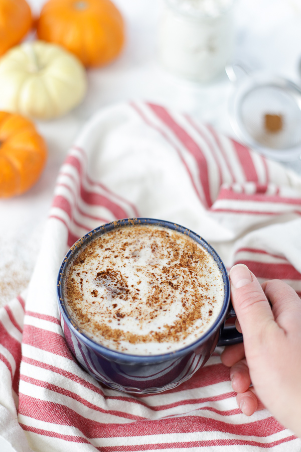 hand holding a blue mug with a frothy vegan pumpkin spice latte