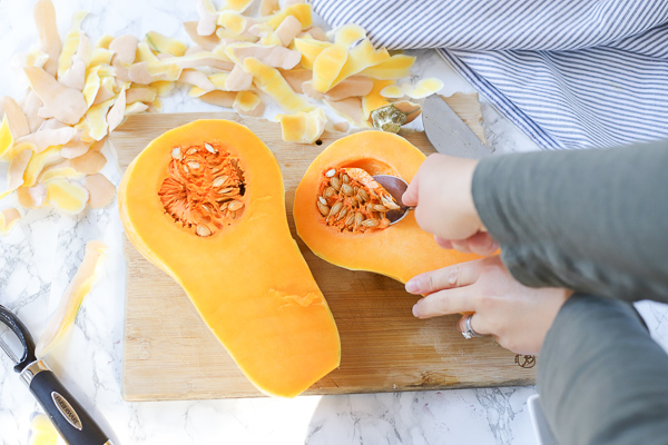 scooping the seeds of a butternut squash on a wood cutting board