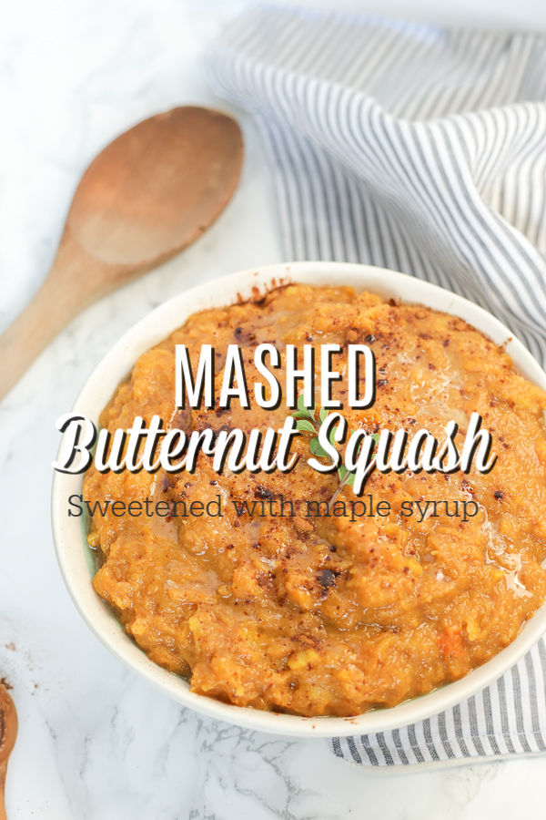 bowl of mashed butternut squash topped with butter and thyme on a marble countertop with a wooden spoon and a striped napkin behind