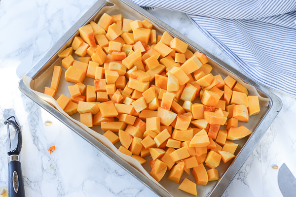 chunks of butternut squash on a parchment paper lined cookie sheet