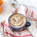 vegan pumpkin spice with a frothy top in a blue mug on top a tan and red stripped towel