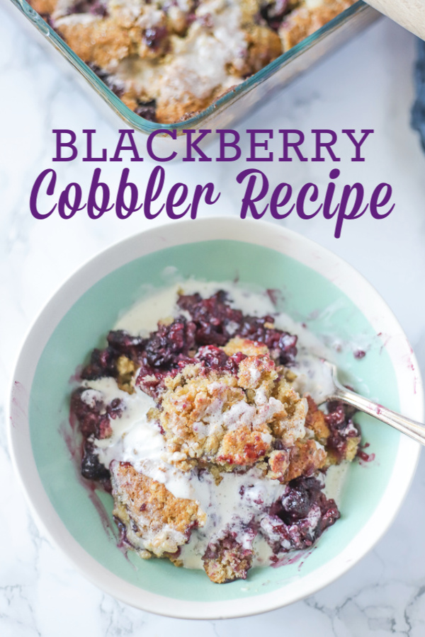 Blackberry cobbler topped with cream in a teal and cream bowl