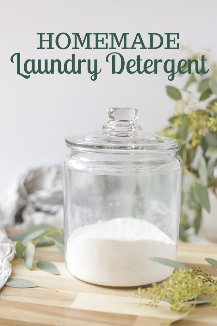 natural homemade laundry detergent on a wood counter with eucalyptus leaves spread around