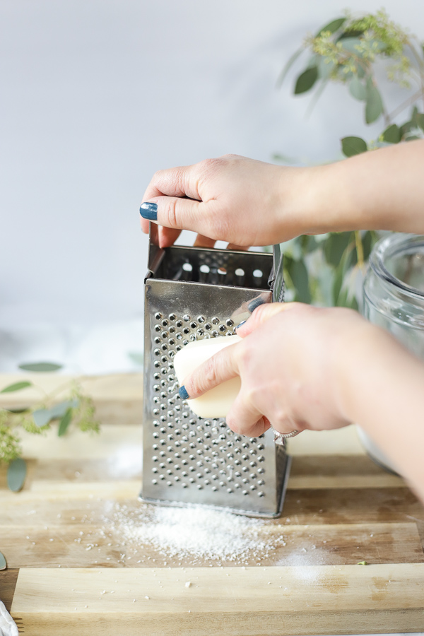 grating a bar of natural soap with a box cheese grater on a wood cutting board for homemade laundry detergent.