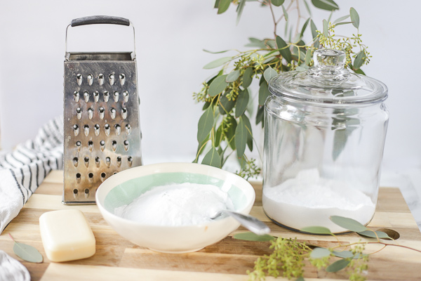ingredients to make homemade laundry detergent on a wood cutting board with a cheese grater, and eucalyptus leaves behind