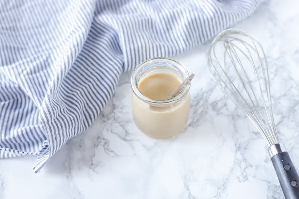 homemade sweetened condensed milk in a jar with a whisk to the right