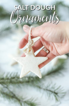 hand holding homemade salt dough ornaments in the shape of a star with twine. Evergreens are in the back
