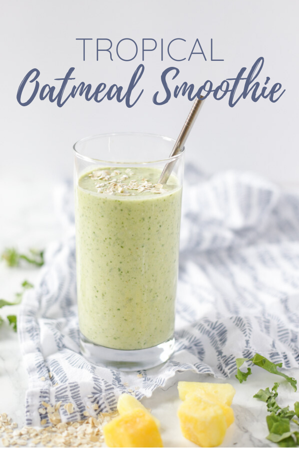tropical oatmeal smoothie in a glass with a metal straw inserted into the smoothie. The glass is on a white and blue patterned napkin with kale, oats, mangos, and pineapples spread around