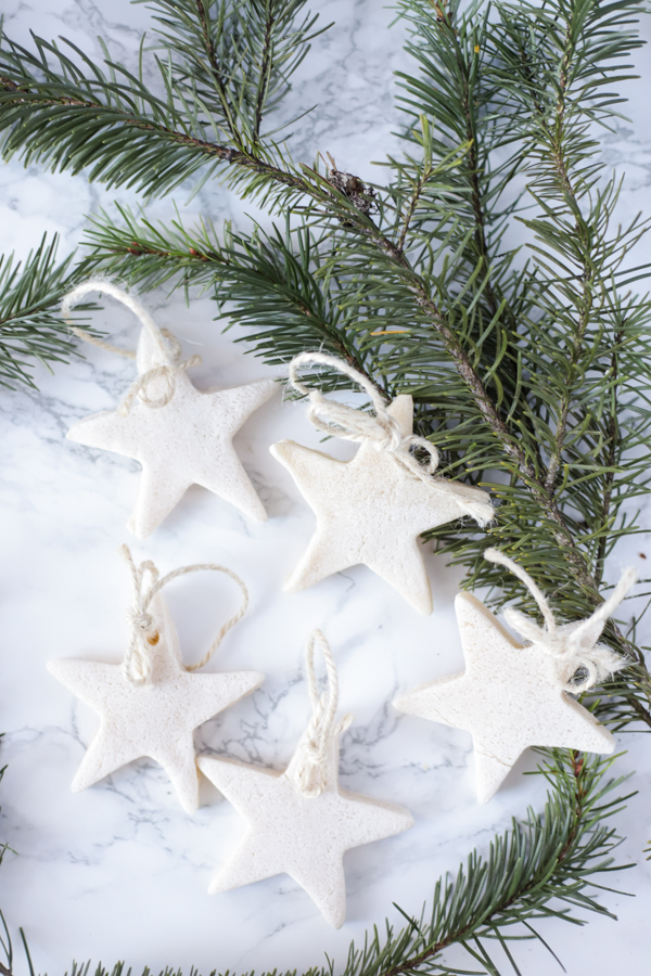 5 salt dough ornaments with twine on a marble countertop with fresh greenery behind