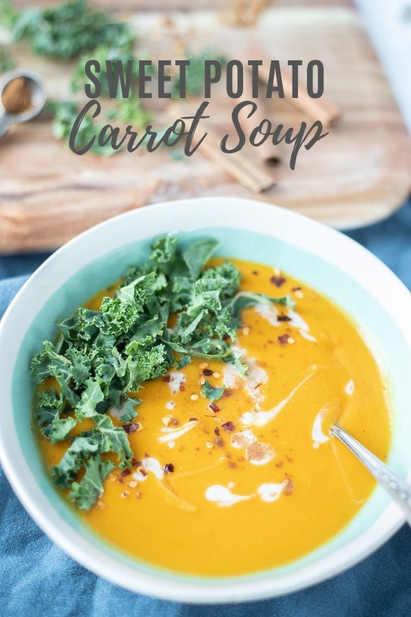 sweet potato and carrot soup with swirls of coconut milk and topped with kale and sprinkled with red peppers