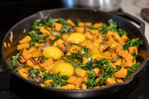 sweet potato hash topped with eggs ready to be put into the oven