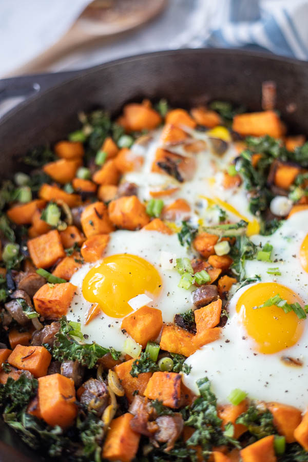 sweet potato hash with sausage topped with eggs in a cast iron skillet