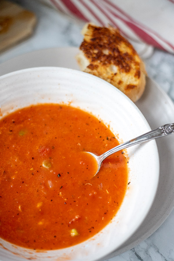 easy tomato soup in a white bowl with grilled cheese on a plate in the background