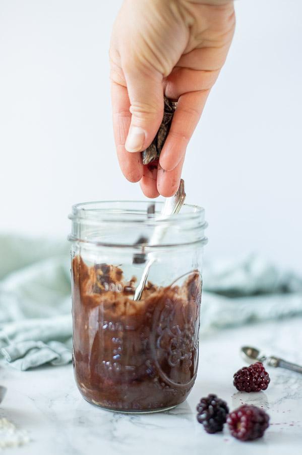 adding chocolate chips to brownie mug cake batter in a mason jar
