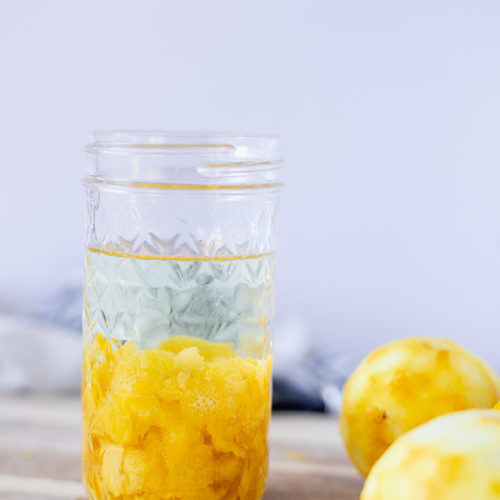 homemade lemon extract in a mason jar on top a wood cutting board with lemons around
