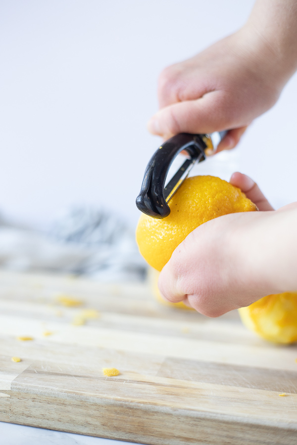 peeling a lemon with a vegetable peeler