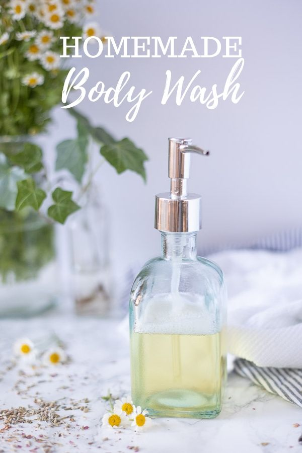 homemade body wash in a glass soap dispenser on a marble countertop with chamomile flowers and dried lavender spread around