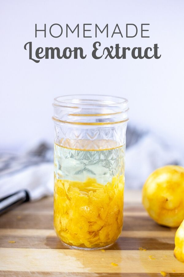 homemade lemon extract in a glass mason jar with lemons around a wood cutting board